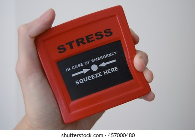 Somebody squeezing an iconic emergency stress cube or ball due to increasing pressure about jobs work money mortgage and everyday problems and a tough day on british transport.