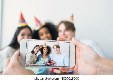 Somebody is taking picture on the phone. There are a girl that has birthday and her friends that are gathered together. They are posing and smiling ro camera.