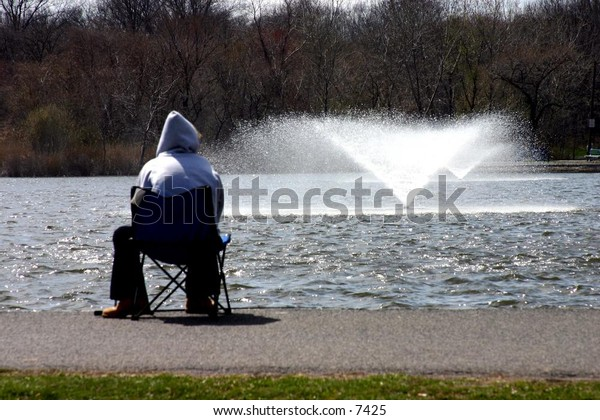 somebody watches fountain on a lake