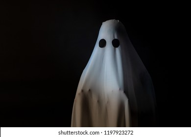 Someone covered with white cloth with big black eyes on black background look like ghost in night. Concept for funny playing in halloween festival.
