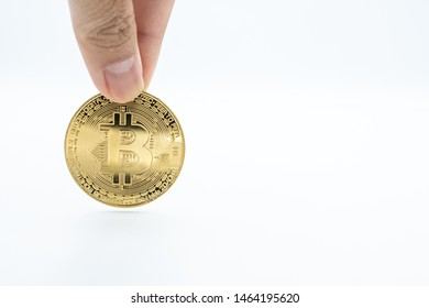 Someone finger with golden Bitcoin isolated on white background. Bitcoin is one of the popular cryptocurrency (a digital assets) , it's the innovative payment network and a new kind of money