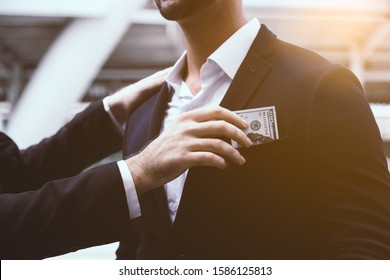 Someone giving bribe, money to businessperson or politician by putting bribe or cash to suit pocket. Businessman get corruption, venal, dishonest, betray his boss, company, colleages, organization
