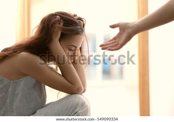 Quelqu'un donnant la main à une femme déprimée à la maison