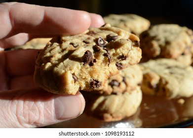 Someone grabbing another bite from a freshly baked chocolate chip cookie.