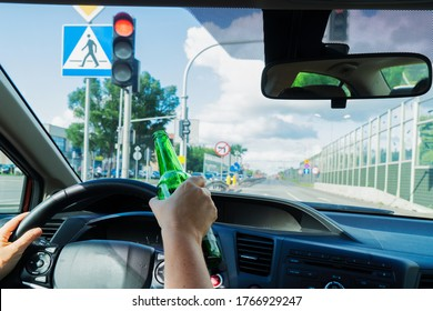 Someone hands driving and holding a bottle with alchohol. Drunk driving concept