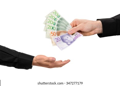 Someone hands over Swedish banknotes in one other mans hand, on white background. New banknotes with new design release year 2015.