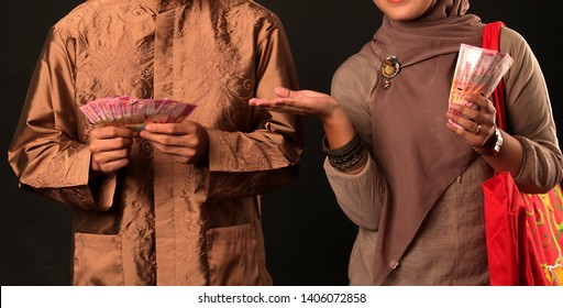 Someone holding money in Indonesian rupiah. Closely to eid mubarak day, usually all moslems employee received THR (Tunjangan Hari Raya) or Eid Mubarak bonuses.
