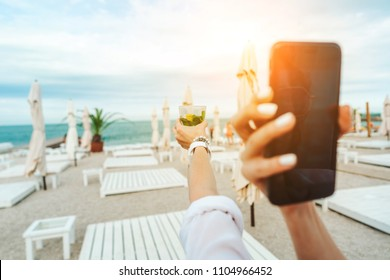 someone is holding a phone and taking a picture of a cocktail