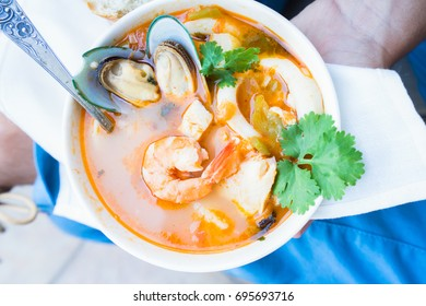 Someone holding plate and eating Bouillabaisse french seafood soup close up
