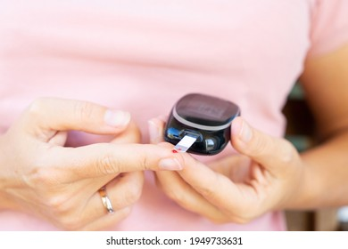 Someone measuring blood sugar level with blood glucose metr, world diabetes day concept