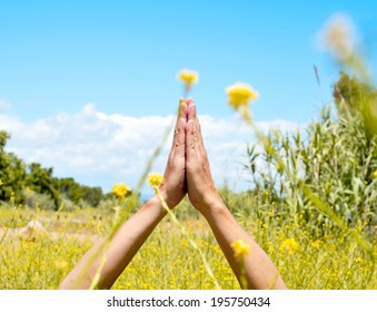 someone meditating with his hands in prayer mudra in a spring field