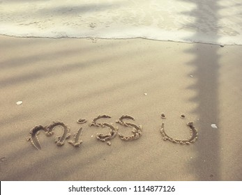 """someone miss someone and write a text """"miss u"""" (miss you) on the beach sand with tree shadow"""