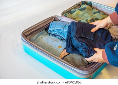 Someone is packing clothes in baggage. It does help to reduce wrinkling.