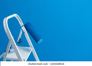 Someone painting wall in blue color, copy space on wall