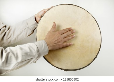 Someone playing a  tambourine against a white background