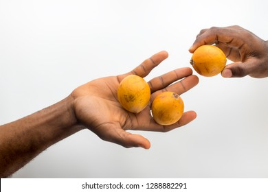 someone sharing agbalumo with another person
