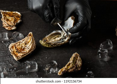 Someone shucking an oyster as water drips out of it. The oyster opening is in focus and the persons hands and background are out of focus.