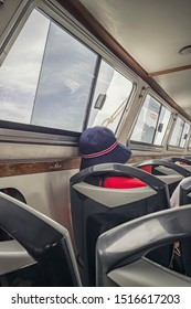 someone sleeping on a ferry with a hat on near a window