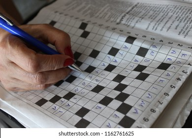Someone is solving crossword puzzle for fun.