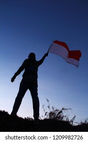 someone stands upright on top of a mountain carrying an Indonesian flag to commemorate the youth oath day