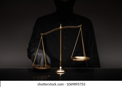 Someone wearing black shirt pressing the imbalance scale on black glass desktop and black background, cheating  in a lawyer's office, Concept of injustice, espionage, partiality, law.