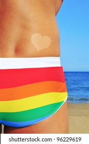 someone wearing a rainbow swimsuit on the beach with a heart-shaped tan mark
