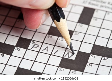 Someone writes the word pain into a crossword puzzle.