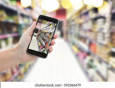 someones hand holding mobile smart phone with augmented reality app in supermarket shop