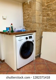 Somerset, UK - 27th March 2018: Installation of new washing machine in a cabinet.