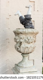 Somerset, Uk, England May 19, 2015: Manakin of a Childs legs upside down inside a large stone garden urn