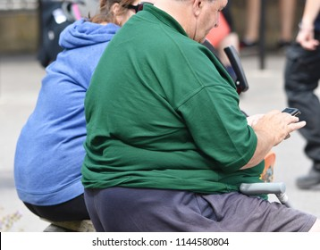 Somerset, UK. July 28 2018. A morbidly obese couple sit on a bench in the street. Almost one in three British adults are now estimated to be obese.