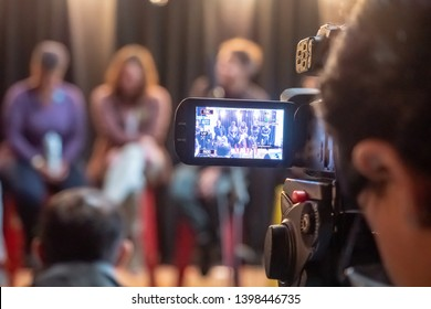 Somerville, MA - April 28 2019: Person filming a panel discussion during an event in Somerville, MA.