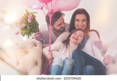 Something worth living for. Three charming young people celebrating mothers day actively while giving a surprise party and making their mom happy