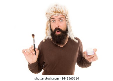 Sometimes fashion goes weird. What if add makeup. Man bearded fashion stylist wear furry hat hold brush for applying makeup. Facial care. Latest fashion trends. Eccentric freak guy isolated on white.