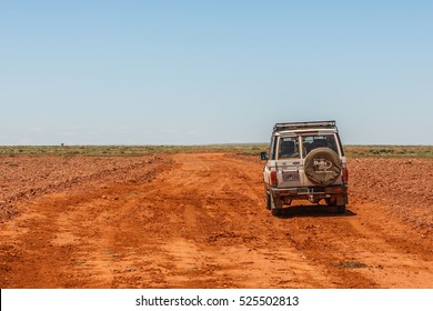 Somewhere along the Oodnadatta Track in South Australia, Australia, 19 december 2011: a Toyota Landcruiser stands still on an open area of bare red land with boulders and gravel against a blue sky