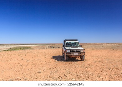 Somewhere along the Oodnadatta Track in South Australia, Australia, 19 december 2011: a Toyota Land cruiser stands still on an open area of bare red rocks and gravel.