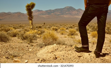Somewhere in Nevada: Western-style colorized shot of very lonesome guy in cowboy boots standing in the desert.