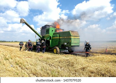 Somme, France, August 2015. Fire of a combine harvester during the wheat harvest. Firefighters working to put the blaze out.