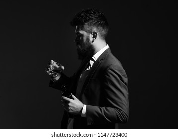 Sommelier with beard tasting alcohol, side view. Drinking concept. Businessman with serious face in suit on black background holding bottle of cognac. Man looking at glass of whiskey or bourbon.