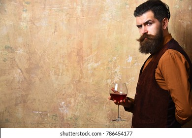 Sommelier with confident face drinks wine glass. Man with beard and mustache holds wine on beige wall background, copy space. Service and profession concept. Degustator with glass of red wine