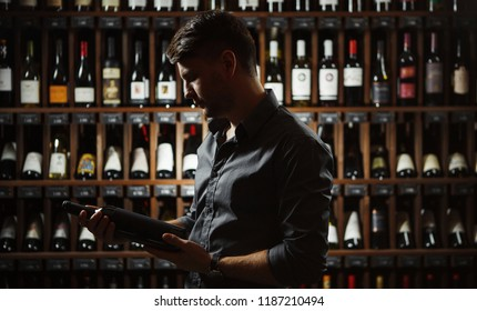Sommelier holding big wine bottle in hands dark