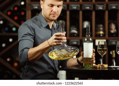 Sommelier holding decanter in hands full of wine