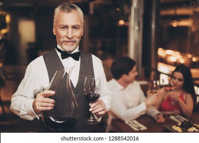 Sommelier is holding glass of wine and decanter, standing near table of couple who are on date. Wine tasting.