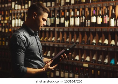 Sommelier is holding and reading a bottle of wine in the cellar.