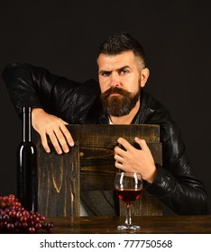 Sommelier leans on wooden chair. Degustator with strict face by wine bottle and dark grapes. Man with beard near glass of wine on dark brown background. Winetasting and degustation concept