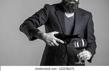 Sommelier man, degustator, winery, male winemaker. Bottle, red wine glass. Waiter pouring red wine in a glas. Beard man, bearded, sommelier, tasting. Pouring red wine from bottle into the wineglass.