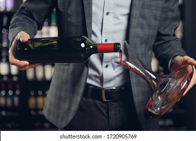 Sommelier man pours red wine into decanter for aeration of taste and aroma.