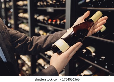 Sommelier man with wine bottle near rack store restaurant with exquisite drinks.