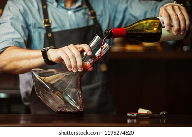 Sommelier pouring out red wine into glass carafe to make perfect color of red wine. Male waiter with decanter at bar counter. Bartender decanting wine without disturbing the sediment