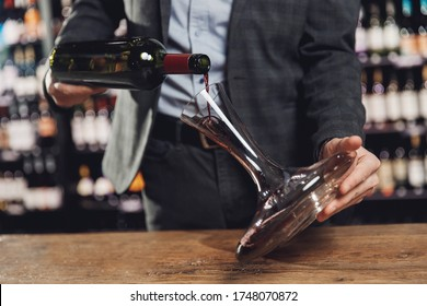Sommelier pouring red wine into carafe decanter to make aeration drink.